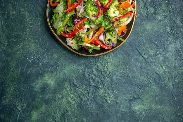 Vista superior de uma deliciosa salada vegana em um prato com vários vegetais frescos em cima em um fundo escuro