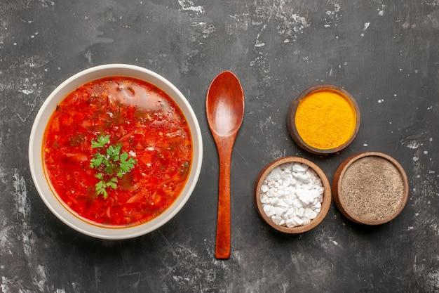 Vista superior de uma deliciosa sopa de beterraba com temperos na superfície escura
