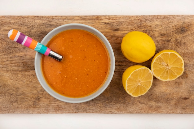 Vista superior de uma deliciosa sopa de lentilhas em uma tigela sobre uma placa de cozinha de madeira com uma colher com limões em um fundo branco