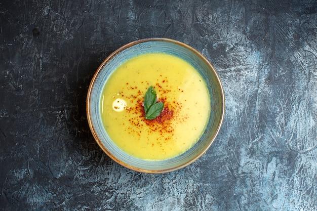 Vista superior de uma deliciosa sopa servida com pimenta e hortelã em uma panela azul sobre fundo escuro