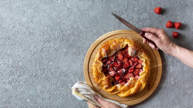 Vista superior de uma deliciosa torta assada com morangos, faca e pano de cozinha em fundo cinza claro