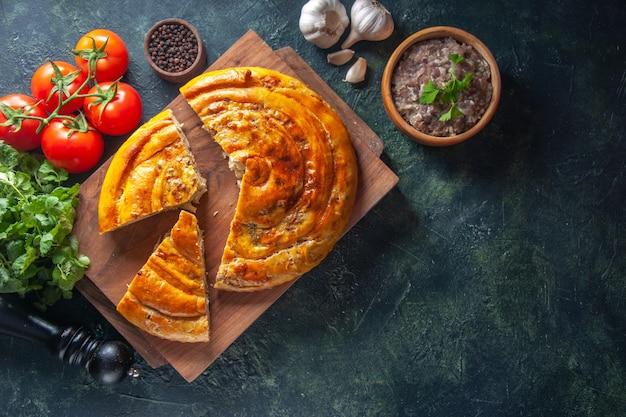 Vista superior de uma deliciosa torta de carne com ingredientes na superfície escura