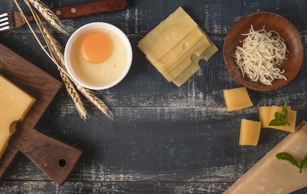 Vista superior de uma deliciosa travessa de queijo com nozes, ovos e farinha em uma mesa com espaço de cópia