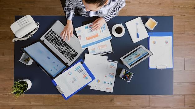 Vista superior de uma empresária analisando a papelada de estatísticas de gerenciamento, digitando a experiência da empresa