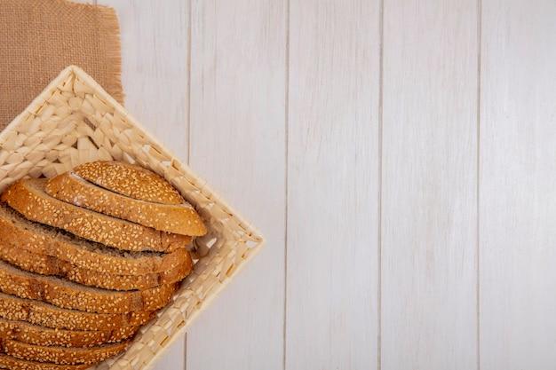 Vista superior de uma espiga de sementes marrom fatiada em uma cesta de saco em um fundo de madeira com espaço de cópia