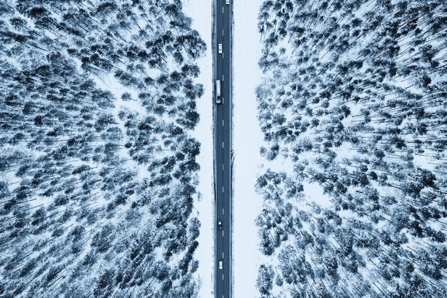 Vista superior de uma estrada cercada por neve e abetos