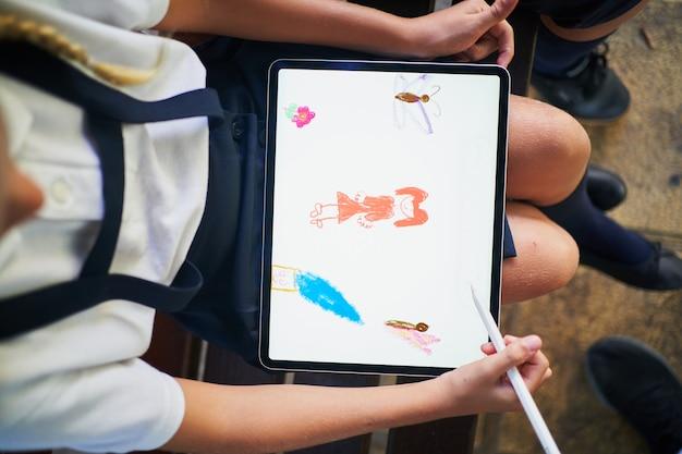 Vista superior de uma estudante espanhola desenhando em um tablet no parque