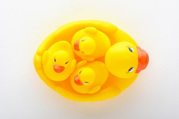 Vista superior de uma família de patinhos de brinquedo amarelos em fundo branco, conceito de maternidade