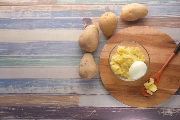 Vista superior de uma fatia de batata crua e ovo em uma tigela