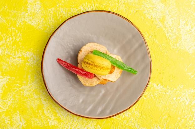 Vista superior de uma fatia de bolo com macaron e marmelada dentro do prato na superfície amarela