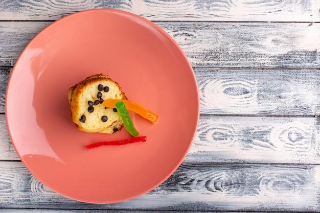 Vista superior de uma fatia de bolo dentro de um prato marrom com chips de choco e marmelada na superfície clara