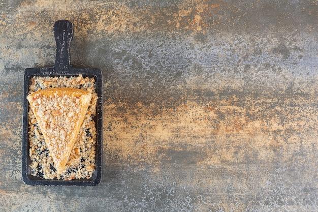 Vista superior de uma fatia de bolo fresco em uma placa de madeira sobre rústico