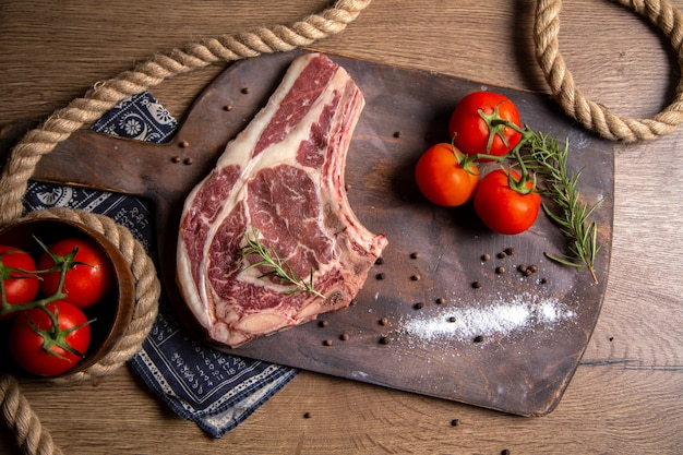 Vista superior de uma fatia de carne crua com tomates vermelhos frescos na foto de madeira crua de refeição