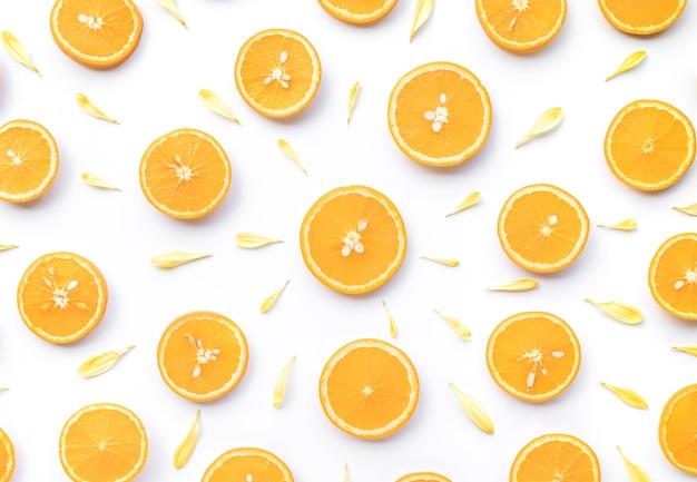 Vista superior de uma fatia de laranja com pétala de flor isolada