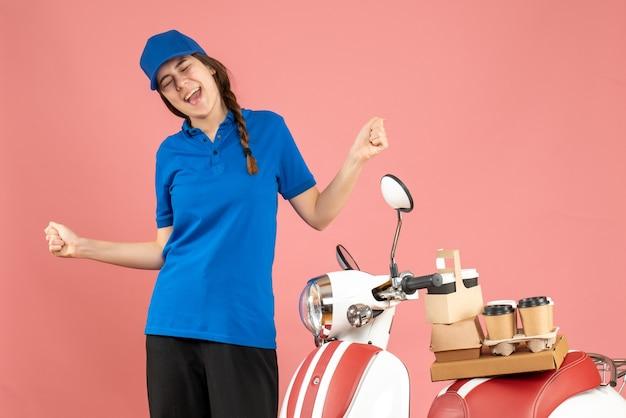 Vista superior de uma feliz mensageira ao lado de uma motocicleta com café e pequenos bolos em um fundo cor de pêssego pastel
