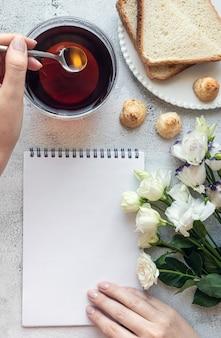 Vista superior de uma folha de bloco de notas em branco e a mão da mulher no ambiente do café da manhã