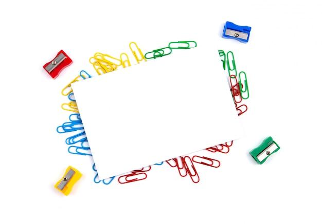 Vista superior de uma folha de papel branca que encontra-se em clipes de papel. near sharpener. copie o espaço para o texto