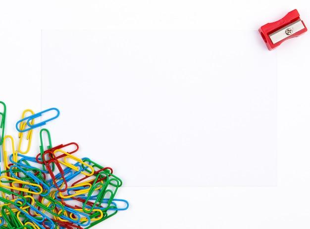 Vista superior de uma folha de papel branca que encontra-se em clipes de papel. perto de apontador vermelho. copie o espaço para o texto