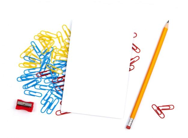Vista superior de uma folha de papel branca que encontra-se em clipes de papel. perto de lápis, apontador. copie o espaço para o texto