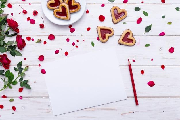 Vista superior de uma folha de papel em branco sobre uma mesa de madeira com biscoitos e rosas