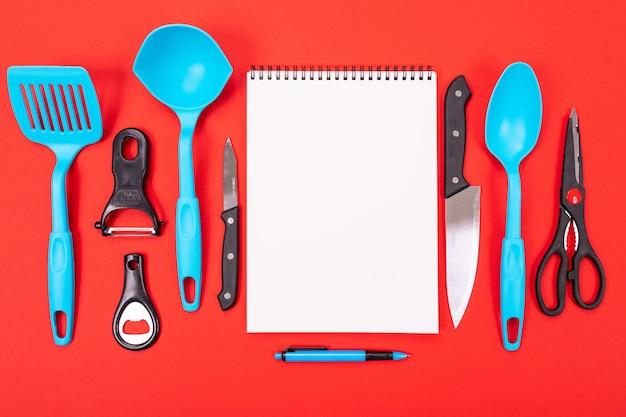 Vista superior de uma folha limpa e utensílios de cozinha ao lado isolado em um vermelho
