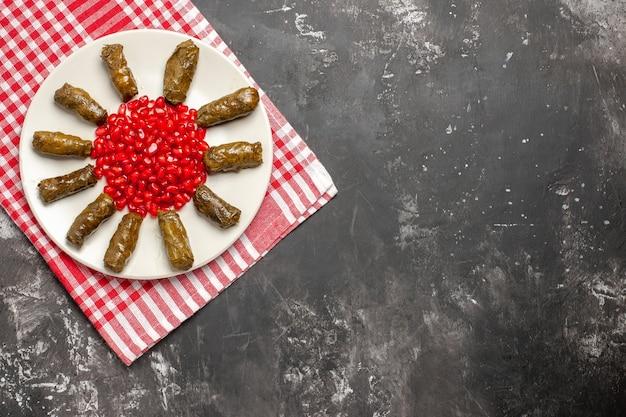 Vista superior de uma folha saborosa de dolma com romãs vermelhas em fundo escuro