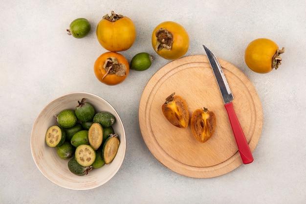 Vista superior de uma fruta madura de meio caqui em uma placa de cozinha de madeira com uma faca com feijoas em uma tigela e caquis isolados em uma superfície cinza