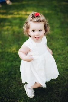 Vista superior de uma garota feliz e fofa com cabelo encaracolado em pé no jardim e olhando para a câmera