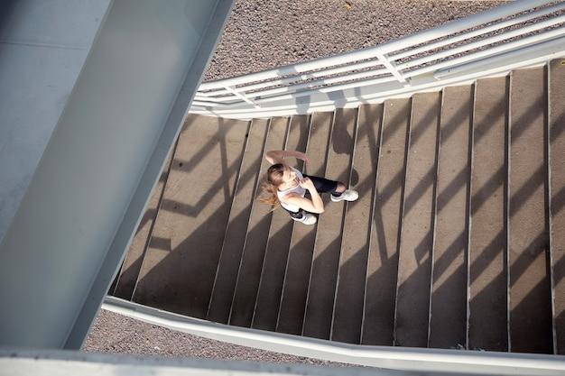 Vista superior de uma garota subindo as escadas