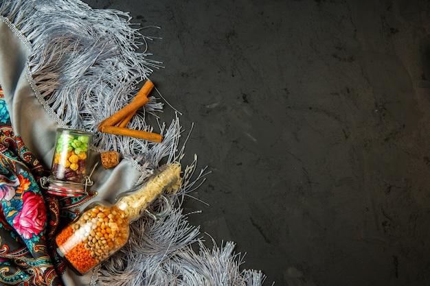 Vista superior de uma garrafa com sementes de milho cru e doces de feijão e canela em pau em um xale com borla com espaço de cópia no preto