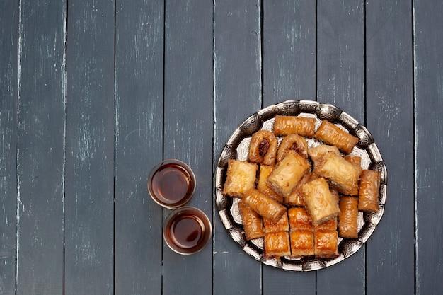 Vista superior de uma grande bandeja de metal com baklava turca em uma mesa de madeira de tábuas