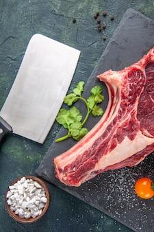 Vista superior de uma grande fatia de carne crua com verduras na superfície escura