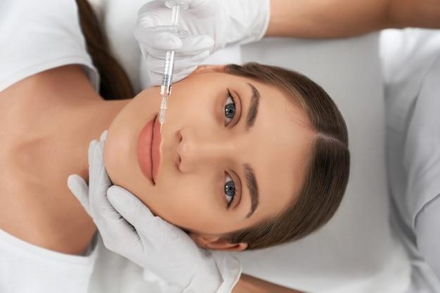 Vista superior de uma jovem atraente nos lábios de aumento de procedimento em esteticista