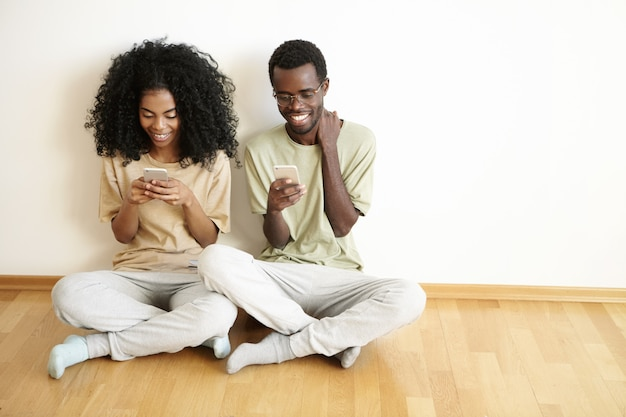 Vista superior de uma jovem bonita com penteado afro, acessando o feed de notícias nas redes sociais