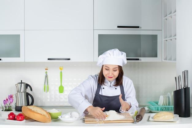 Vista superior de uma jovem chef feminina de uniforme, em pé atrás da mesa, cozinhando na cozinha branca