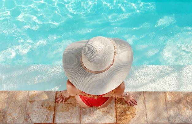 Vista superior de uma jovem com maiô vermelho e chapéu de palha relaxando perto de uma piscina com as pernas na água