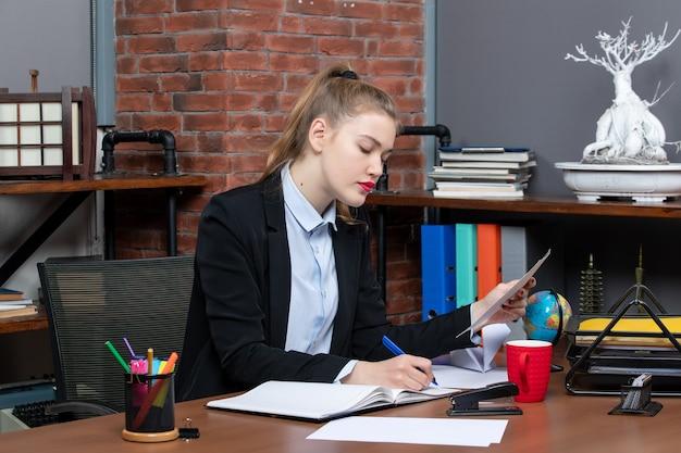 Vista superior de uma jovem concentrada sentada à mesa e escrevendo em um documento no escritório