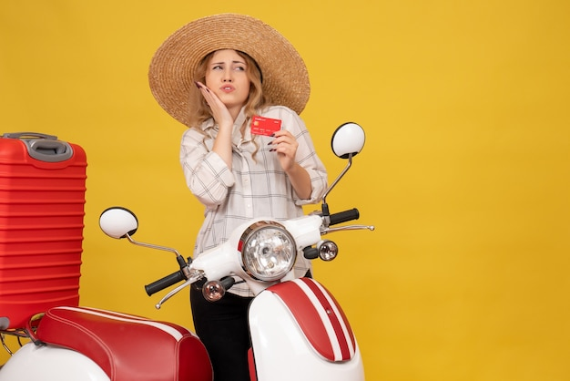 Vista superior de uma jovem curiosa de chapéu, recolhendo a bagagem, sentado na motocicleta e segurando o cartão do banco