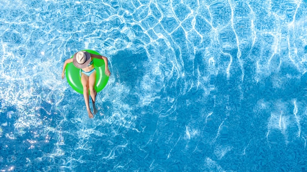 Vista superior de uma jovem em um anel inflável verde em uma piscina