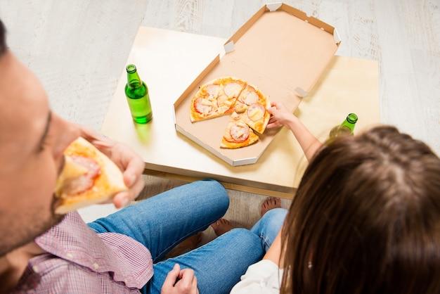 Vista superior de uma jovem família feliz assistindo tv com cerveja e pizza