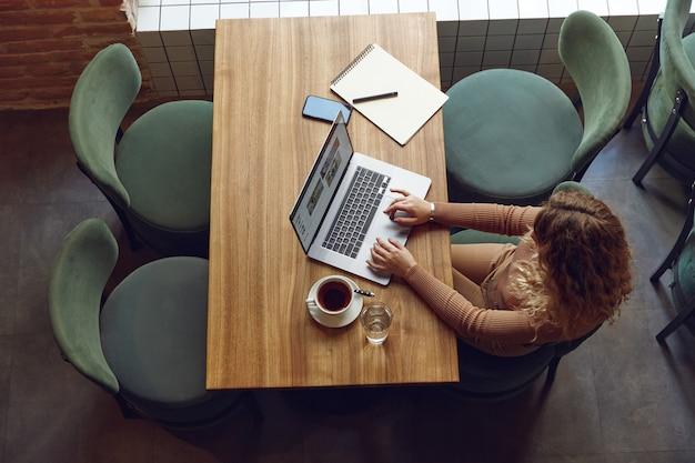 Vista superior de uma jovem loira com cabelo encaracolado, sentada em um café aconchegante e trabalhando em um laptop moderno