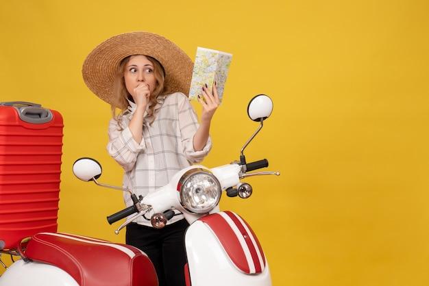 Vista superior de uma jovem maravilhada com um chapéu, recolhendo a bagagem, sentado na motocicleta e segurando o mapa