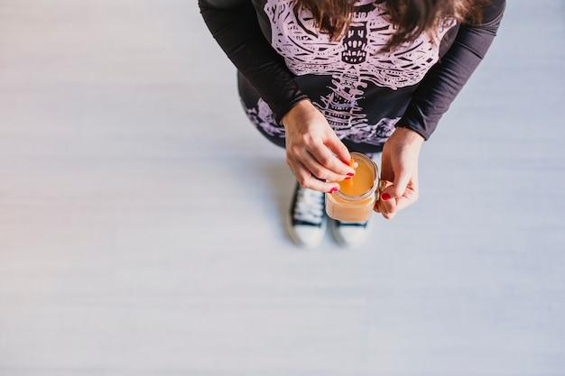 Vista superior de uma jovem mulher bonita segurando suco de laranja. vestindo uma fantasia de esqueleto preto e branco. conceito de dia das bruxas. interior