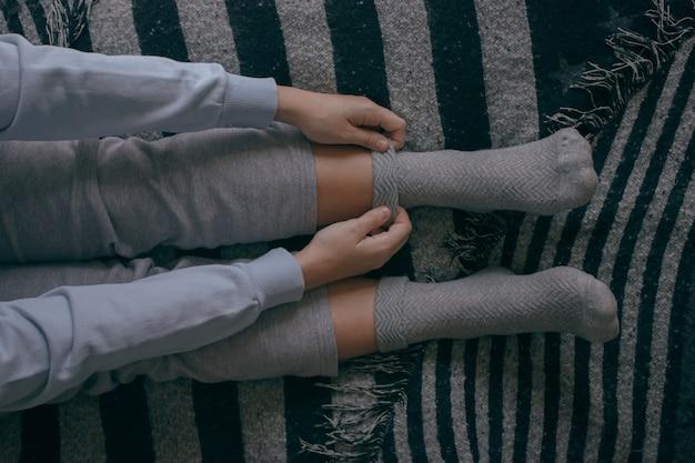 Vista superior de uma jovem mulher calçar algumas meias em um dia frio para passar em casa cozy home concept.