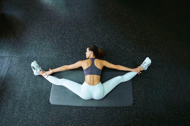Vista superior de uma jovem mulher de aptidão flexível em roupas esportivas, sentada no cordão transversal, alongando os músculos do corpo após o treino na academia. esporte e conceito de estilo de vida saudável