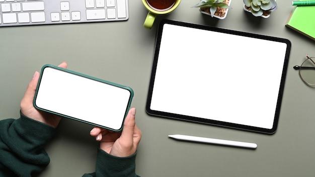 Vista superior de uma jovem mulher de suéter verde segurando um smartphone e um tablet digital na mesa do escritório