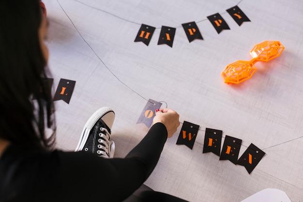 Vista superior de uma jovem mulher faz guirlanda de halloween. diy criativo. festa de projeto de decoração para casa.