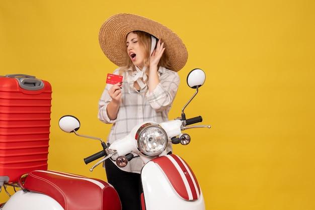 Vista superior de uma jovem nervosa com chapéu, recolhendo a bagagem, sentado na motocicleta e segurando o cartão do banco