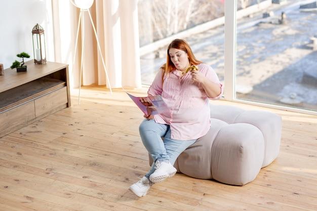 Vista superior de uma jovem positiva lendo uma revista de moda enquanto relaxa em casa
