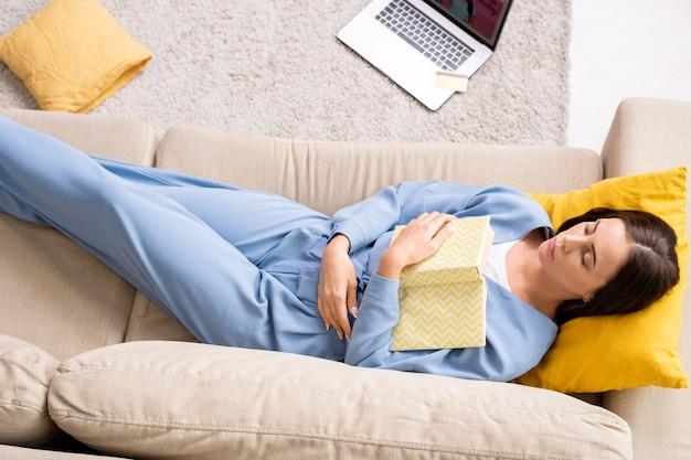 Vista superior de uma jovem repousante de pijama azul segurando um livro aberto no peito enquanto relaxa no sofá com a cabeça no travesseiro amarelo depois do trabalho